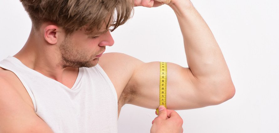 man measuring his bicep with a tape measure