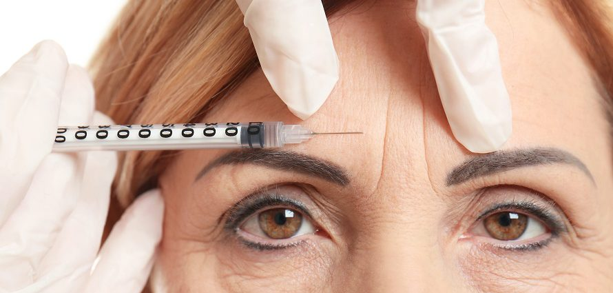 middle aged woman receiving botox injection to forehead