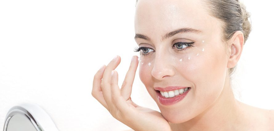 smiling female applying eye cream