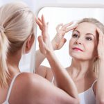 middle age woman looking at her face in mirror