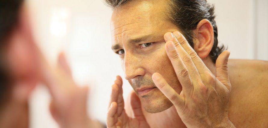 man looking at his wrinkles in mirror