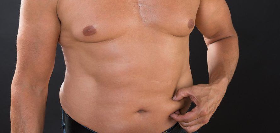 overweight man pinching stomach fat